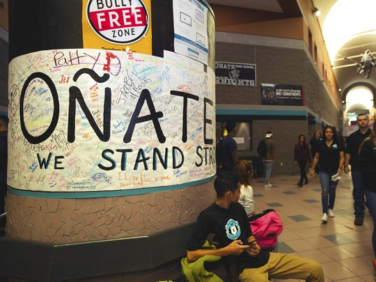 """Oñate High School students made a poster, left, reading """"Oñate Knights We Stand Strong"""" to show support for the football team."""