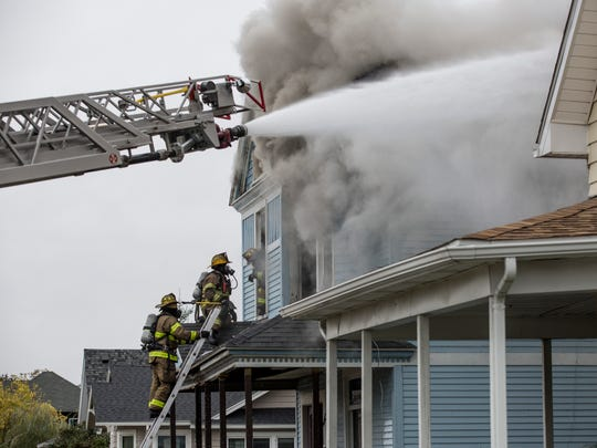 Port Huron, Port Huron Township and Marysville firefighters work the scene of a house fire Oct. 26, 2016, in the 1200 block of Water Street in Port Huron.