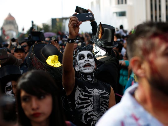 A man in costume takes a selfie during a Day of the Dead parade along Mexico City's main Reforma Avenue, Saturday, Oct. 29, 2016. Hollywood movies, zombie shows, Halloween and even politics are fast changing Mexico's Day of the Dead celebrations, which traditionally consisted of quiet family gatherings at the graves of their departed loved ones bringing them music, drink and conversation.