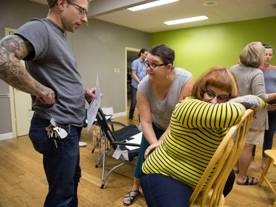 Hillary Melchiors shows Clint and Heather Vaught some of the best ways to help comfort an expectant mother during the pains of labor at Melchiors' September Lamaze Childbirth Education class at Little Ants in Evansville.