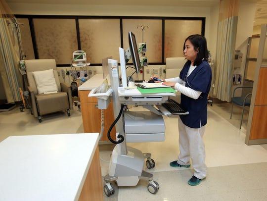 Registered Nurse Kathleen Jamandre charts a patient