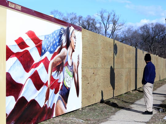 """Mount Vernon resident Lennox Dressikie, 55, stands by the """"Wall of Legends,"""" a wall that honors Mount Vernon athletes at Memorial Field in Mount Vernon, Jan 26, 2017. Olympic runner Deajah Stevens was the first athlete featured on the wall."""