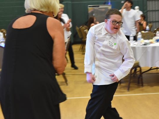 Parker Demirco, 13, dances up a storm while his buddy, Charlotte Warner, cheers him on inside the gymnasium of New Hope Ministries on Feb. 10, 2017. The Night to Shine prom sponsored by the Tim Tebow Foundation hosted a night to remember for thousands of special needs individuals across the globe.