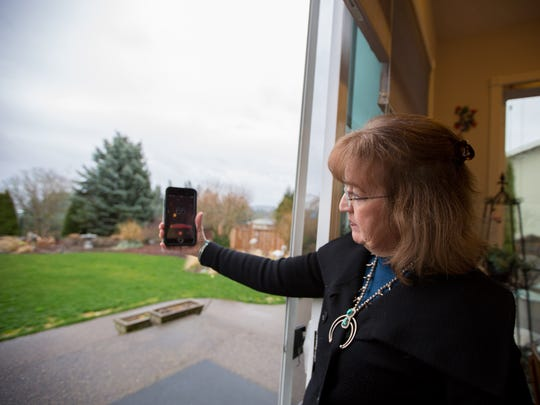 Betty Buholts uses a smart phone app to measure the noise level from her home on Friday, March 3, 2017, along Interstate 5 in South Salem. Buholts' home is among four that were originally supposed to benefit from a sound wall that is nearing construction. However, a noise analysis has now excluded those homes from the project due to a retaining wall that officials say acts as a noise barrier.