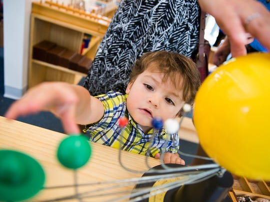 Jace Marcozzi, 1, plays with a solar system model during the grand opening of the Garden School of Naples on Friday, May 19, 2017, in East Naples. Jace will attend the school in August.