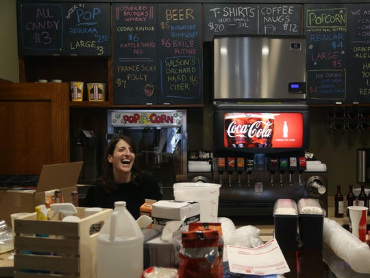 Rebecca Fons laughs from behind the concessions counter of The Iowa on the afternoon before the theater opens on Wednesday, May 24, 2017, in Winterset.