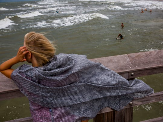 Angelina Kovago, 7, of Toronto, watches surfers off the Naples Pier as Tropical Storm Emily passes over Florida on Monday, July 31, 2017.