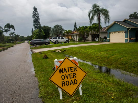 A sign warned of flooding in North Naples as Tropical Storm Emily passed over Florida on Monday, July 31, 2017.