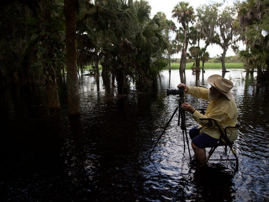 Iconic landscape photographer Clyde Butcher prepares to take a photo in Myakka River State Park in Sarasota, Fla., on Thursday, Aug. 3, 2017. This was his seventh attempt to take this image at this particular location, and he finally captured it. Butcher is recovering from a stroke he had in May, so instead of using his large format film camera, he is using a smaller digital camera and a walker with a seat to help him get around.