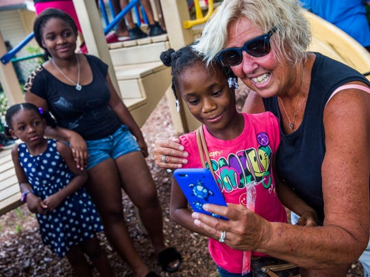 Third-grade teacher Cheri Gimenez takes a selfie with rising fourth-grader Doruna Charles as educators from Manatee Middle and Manatee Elementary School visit students in Habitat for Humanity Communities in Naples on Wednesday, Aug. 9, 2017.