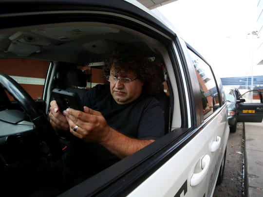 Laurence Anouya, 54, of Hazel Park, who drives for Aref Metro Cab, sits in his taxi playing Candy Crush waiting for a fare in front of the Motor City Casino Hotel.