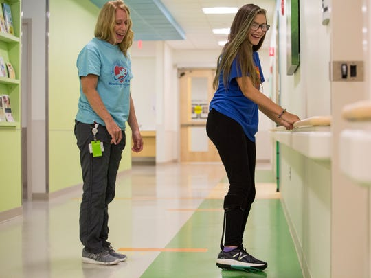 Charlotte Johnson, right, goes through therapy exercises at Nemours/Alfred I. duPont Hospital for Children to strengthen her core and legs after she suffered a spinal stroke a little over a year ago.