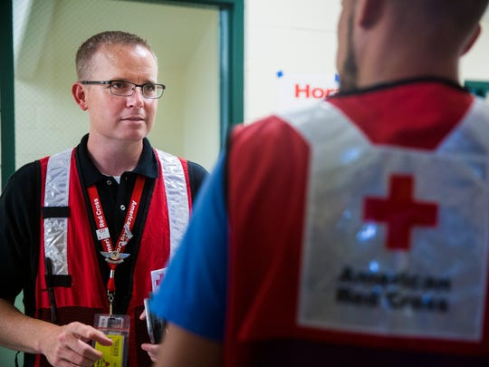 Bryan Hartmann, a Red Cross shelter manager, talks with another volunteer at the emergency shelter at the Estero Community Park Recreation Center on Sunday, Sept. 24, 2017. Hartmann has spent more than a week managing the emergency shelter following Hurricane Irma.