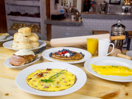 A selection of egg dishes with biscuits, pancakes and a cinnamon roll from Scrambled Jakes Restaurant