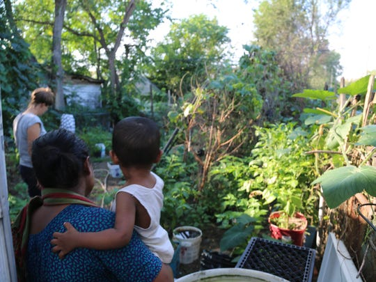 Minara Begum carries her son, Hussain, to her productive backyard garden in Detroit's Banglatown, where she is part of a women-run network of gardeners and cooks that call themselves Bandhu Gardens.