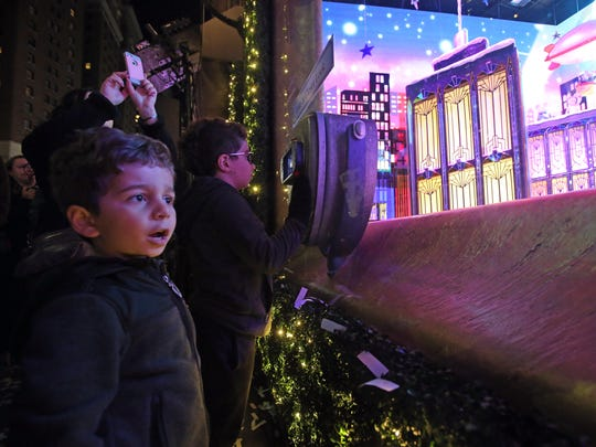 "Elias Ghannam, 5, and his brother, Alexander, 8, looks at the unveiled holiday window display called ""The Perfect Gift Brings People Together"" at Macy's Herald Square in Manhattan Nov. 16, 2017."