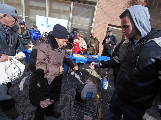 Hermia Lopez of Yonkers receives a turkey from volunteer