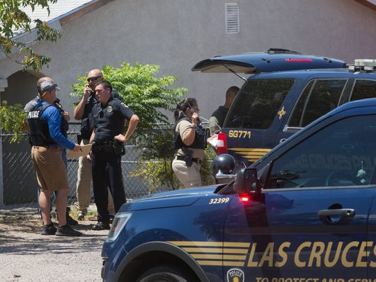 Las Cruces Police officers gather near the end of Arizona Avenue, where they set up a staging area before SWAT team members move into a location on Monday July 17, 2017.