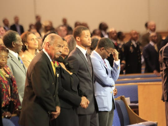 U.S. Rep. John Conyers, his wife Monica Conyers and their sons, Carl Conyers and John Conyers III, stand for the National Anthem at Greater Grace Temple in Detroit in 2013.