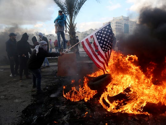 A Palestinian protester burns the US flag during clashes