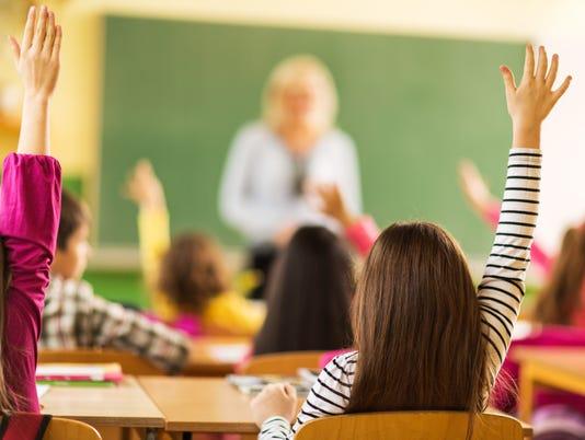 Rear view of school kids raising their hands at school.