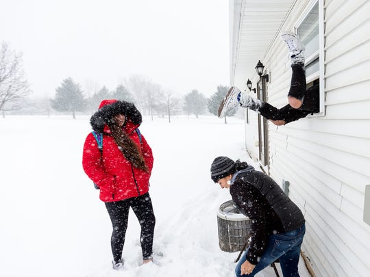 "Alysia Powless, from left, and Tina Christjohn laugh as Jojo Powless climbs through a window of his house after being locked out in Oneida, Wis., Wednesday, December 13, 2017. Jojo Powless lit the ""sacred fire"" initially, which his father Joey Powless said was symbolic of the innocence of young people and the power they have to influence the community for the better."