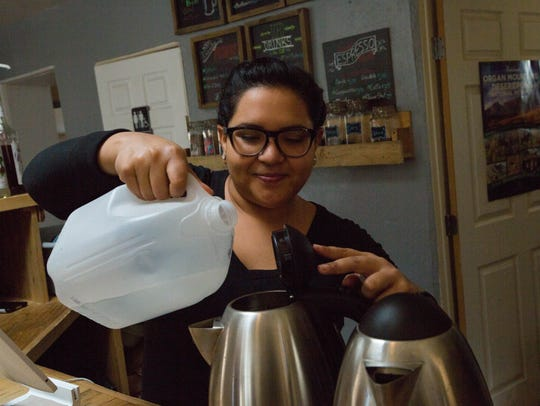 Valerie Mirelez, a barista at Beck's Roasting House and Creamery, pours water into electric tea pots in preparation for customers. Wednesday January 10, 2018.