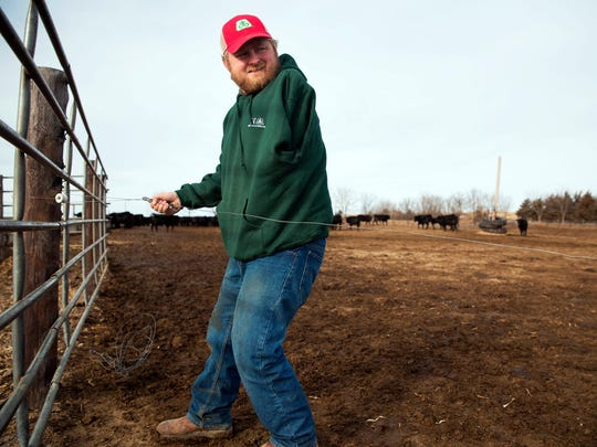 Kyle Lammers repairs an electric fence Friday, Jan 19, 2018, in Hartington, Neb. In November of 1998, Lammers lost his left arm in a farming accident when he was 13 years old.