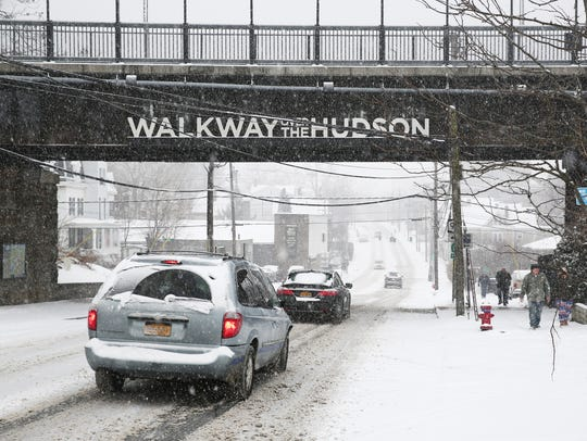 Cars and pedestrians pass under the Walkway Over the