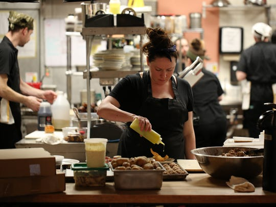 Chef Kate Williams plates a dish in the kitchen of