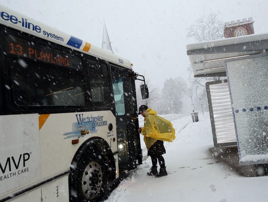 4:04 p.m.: A commuter boards the bus during a snowstorm