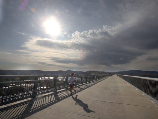 A runner makes her way over the Walkway Over the Hudson.