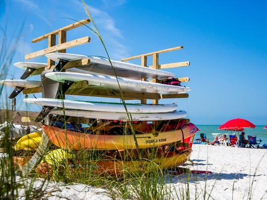Stacks of kayaks and paddle boards on the beach at