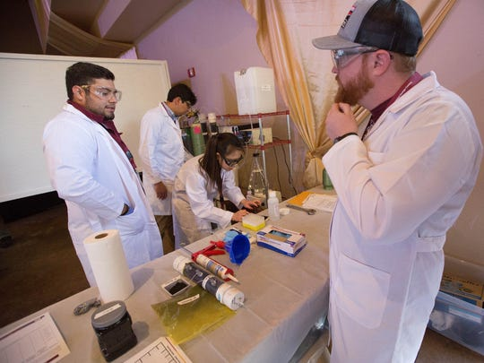 Graham Chapman, right, Xiao Cheng, center, Joel S. Valdez, left, and Luis Garcia, center left, all New Mexico State University students, work to get their demonstration of a system they designed to remove Carbamazepine from a watershed, to judges at the 28th Annual WERC Environmental Design Contest. Tuesday, April 10, 2018 at the Farm and Ranch Museum. The design contest brought together 25 teams from 12 different universities.