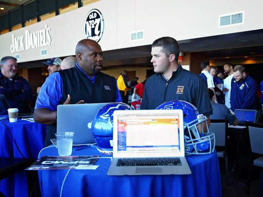 Roc Batten, head coach at Battle Ground Academy in Franklin, talks to an assistant coach from Mercer University in Macon, Ga. The fair started in 2015 to give unsigned high school players a chance to continue their football careers in college.