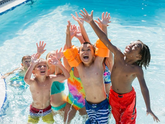 Multi-ethnic group of children playing in swimming pool