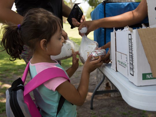 Vivian Corral, 3, picks up a lunch pack from the Families and Youth Incorporated summer free lunch program at Young Park, Wednesday June 6, 2018.