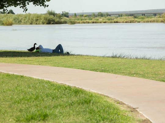 Marcos Castro rests in the grass along the Rio Grande Trail in La Llorona Park as a duck waddles around him, Friday July 20, 2018. A proposed bond would finish connecting the trail to the Out Fall Channel Trail that runs under Main street. Friday July 20, 2018.