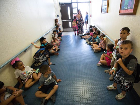 Students in the K-3 Plus program line the hall way leading to the exit at Central Elementary School, Monday July 23, 2018. The students were told to wait until their parents arrived outside before leaving the school due to high temperatures. Bus services were stopped in the district as well due to the heat. Which is projected to be 104 Monday.
