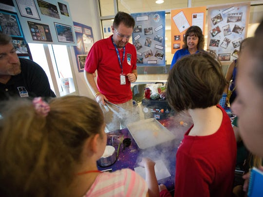 Norm Jensen, center, along with Kathleen Guitar, right, and Pat Switzer, from the Challenger Learning Center, show kids how liquid nitrogen changes from a liquid to a gas by pushing a ping pong ball around a cookie sheet, teaching children the principles of physics.