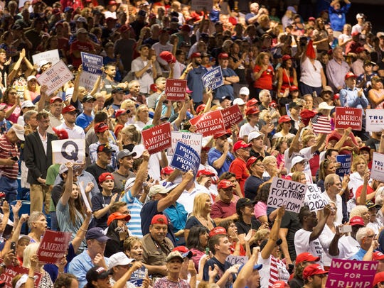People cheer as President Donald Trump speaks at the