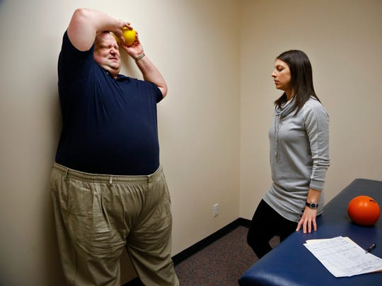 Daniel P. Finney works on strengthening his back with physical therapist Stefanie Kirk on March 31 in Des Moines.