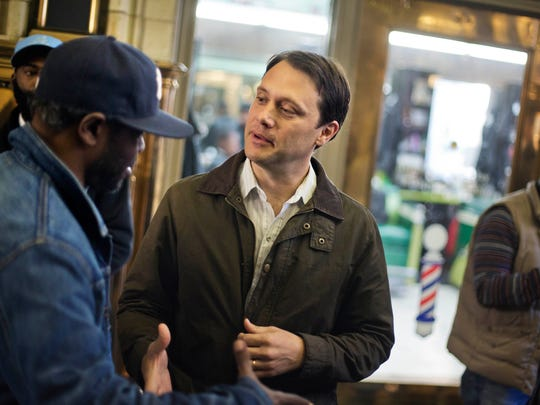 Georgia Democratic gubernatorial candidate Jason Carter, right, greets patrons during a campaign stop at Vintage Barbershop, on Nov. 3, 2014, in Atlanta.