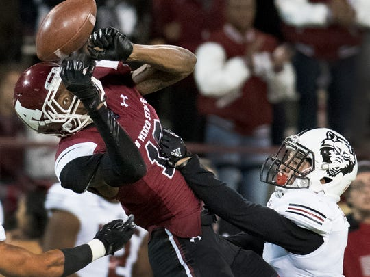 New Mexico State receiver Jaleel Scott keeps his eye on the ball over the defense of Arkansas State's BlaiseTaylor during first quarter action Saturday night at Aggie Memorial Stadium.