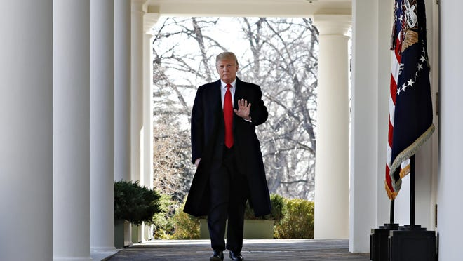 President Donald Trump waves as he walks through the Colonnade from the Oval Office of the White House on arrival to announce a deal to temporarily reopen the government, Jan. 25, 2019, from the Rose Garden of the White House in Washington.