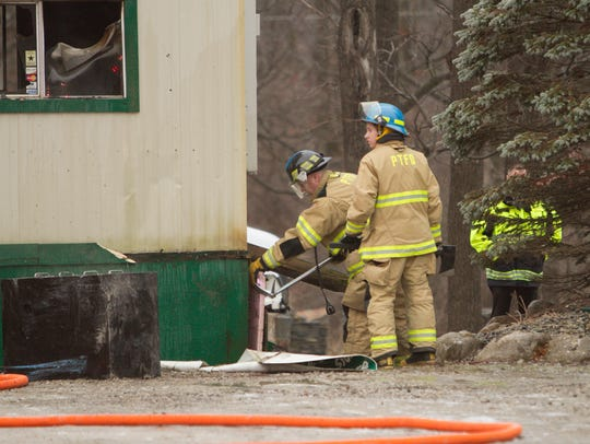 Firefighters remove the siding from a trailer that