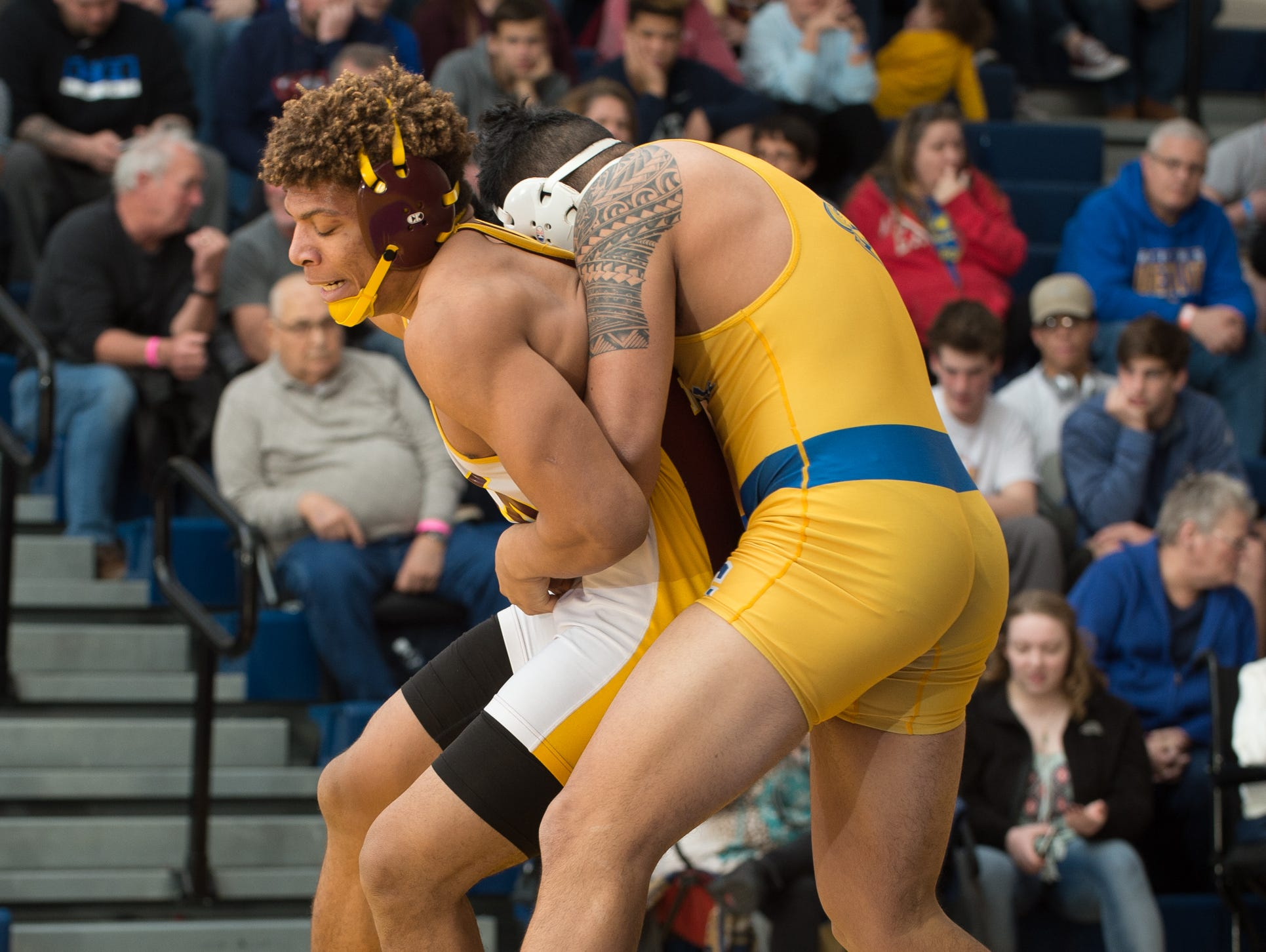 Milford's Dominic Covington, left, works to get out of a hold by Sussex Central's Johnny Morris battle in the 220 pound championship match at the Henlopen Conference wrestling tournament at Sussex Central High School.