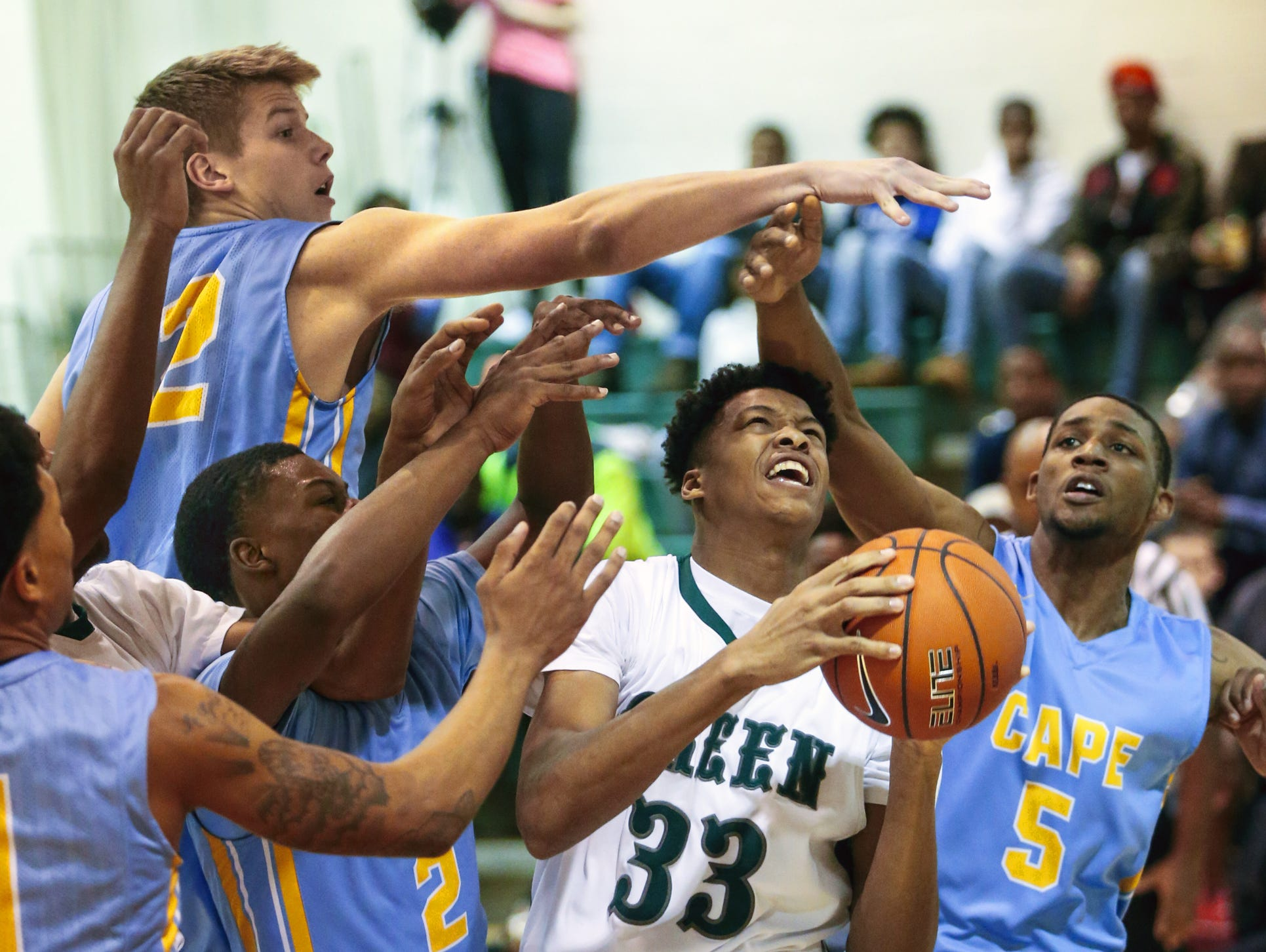 Mount Pleasant's KVonn Cramer (33) is surrounded under the basket by Cape Henlopen's Ian Robertson (top) and (from left) Jerry Harden, Cory Barnes and Randy Rickards in the first half of Mount Pleasant's 50-47 home win in the second round of the DIAA state tournament Friday.