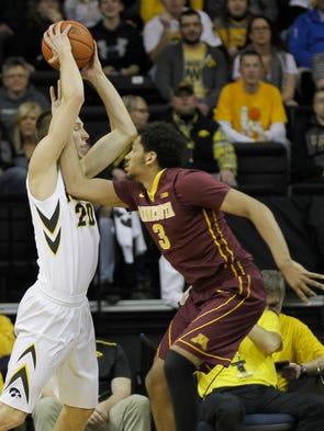 Iowa's Jarrod Uthoff pulls down a rebound over Minnesota's