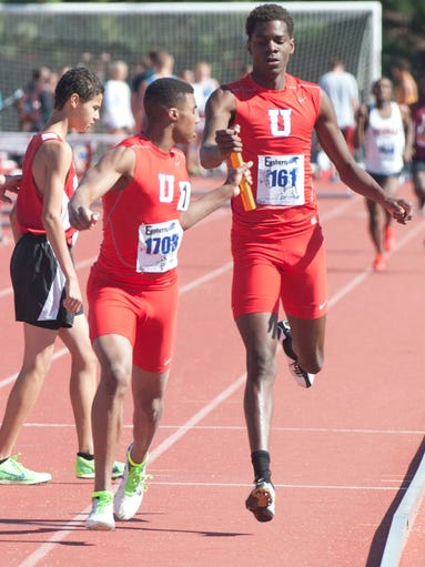 Memphis University's Clayton Turner, right, hands the baton off to Carlton Orange, left, in the boys 4X800 meter relay at the Eastern (High School) Relays Track Meet at the University of Louisville. 26 April 2014